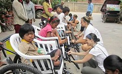 Brandy_and_Emilee_with_Cambodians_fixing_wheelchairs