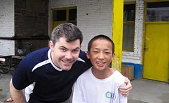 China_volunteer_man_with_local_boy_outside_yellow_door