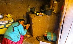 Cusco_062913_Harleigh_Jones_woman_putting_wood_in_stove_good_photo