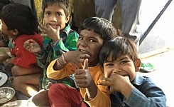 India_122512_Jeb_Butler_three_local_children_eating_good_photo