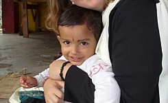 India_female_volunteer_with_young_Indian_child_in_her_lap_good_photo