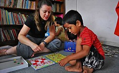 India_volunteer_playing_games_with_child_good_photo